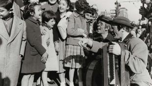 Foto en blanc i negre de pallassos, un amb acordió, fent riure els nens a la desfilada del circ