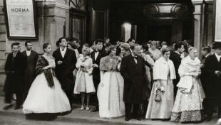 Foto en blanc i negre de la gent molt elegant a la porta del teatre del Liceu abans de la funció