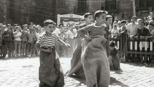 Foto en blanc i negre de nens fent una cursa de sacs a les Festes de Sant Roc
