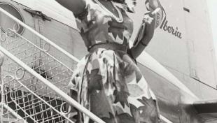 Foto en blanc i negre de Miss Europa saludant, somrient i baixant les escales de l'avió a la seva arribada a l'aeroport de Prat