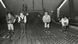 Foto en blanc i negre de quatre joves esquiant sense neu al Saló de Turisme i esport a Montjuïc