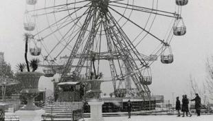 Foto en blanc i negre. Es veu la nòria del Tibidabo i gent passejant envoltada de neu