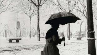foto en blanc i negre. Es veu una vianant amb paraigües i cistell camina per un carrer ple de neu