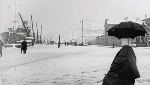 Foto en blanc i negre. Es veu a primer terme un ninot de neu amb abric i paraigües, el moll tot nevat i al fons un vaixell amb neu