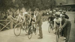 Foto en blanc i negre dels ciclistes al començament de la pista de velocitat a les sis hores de la cursa de Sants