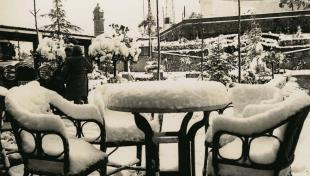 Foto en blanc i negre. Es veuen dues cadires i una taula de la terrassa de bar del Tibidabo amb 15 centímetres de neu al damunt
