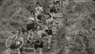 Foto en blanc i negre dels ciclistes que porten bicicletes a l'esquena per pujar un turó durant el Campionat de Catalunya per a vianants amb bicicleta. Drecera de Vallvidrera
