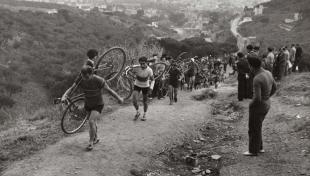 Foto en blanc i negre dels ciclistes que porten la bicicleta a l'esquena per pujar un turó