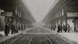 Foto en blanc i negre, vista des de les vies del tren la gent a la inauguració de l'Estació de Sants