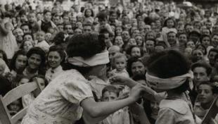 Foto en blanc i negre de nens jugant amb els ulls tapats a la Festa Major de Parel·lel
