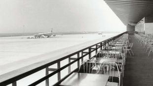 Foto en blanc i negre de les taules buides i l'avió  aturat al fons, a causa de la aturada dels aeroports en protesta pel segrest d'avions.