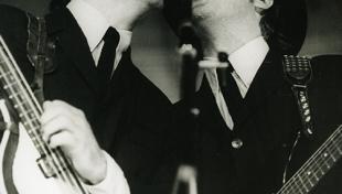 Foto en blanc i negre. Es veuen cantant els membres dels Beatles John Lennon i Paul Mccartney  en el concert de Barcelona
