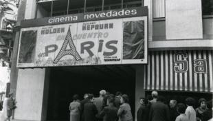 Foto en blanc i negre de l'entrada del cinema Novedades amb gent fent cua a la porta