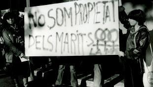 Foto en blanc i negre. Es veu 2 noies en una manifestació feminista que porten pancarta on diu : no som propietat dels marits