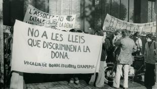 Foto en blanc i negre. Es veu gent amb pancartes en una manifestació feminista