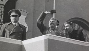 Foto en blanc i negre de Francisco Franco presidint una desfilada militar, saluda amb la mà