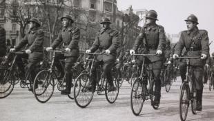 Foto en blanc i negre de cinc ciclistes de la unitat ciclista de l'exèrcit durant una desfilada