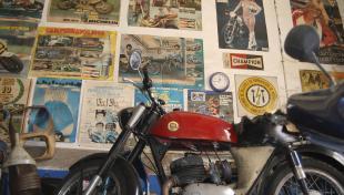 Foto a color. Es veu moto en primer terme i al darrera a la paret del taller calendaris i fotos enganxades
