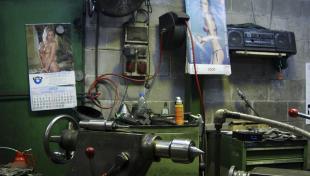 Foto a color. Es veu taller amb màquines en primer terme i al darrera a la paret del taller eines ,calendaris i fotos enganxades
