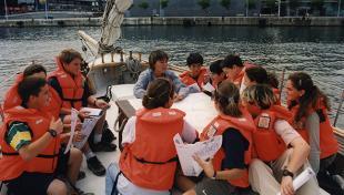 Foto color. Es veu una activitat educativa amb nens que porten armilla salvavides taronja navegant en un veler pel port.