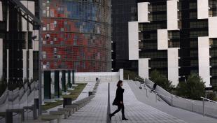 Es veu un noi caminant per la plaça de les Glòries Catalanes i al fons, hi ha els edificis de la Torre Agbar i l'hotel Diagonal Barcelona
