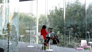 Es veu noia amb ordinador asseguda a l'interior de l'edifici Media_TIC davant de vidriera gran. A l'exterior es veuen arbres i vegetació