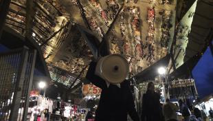 Fotografia del sostre mirall del mercats dels Encants on es veu els visitants del mercat reflectits en el sostre