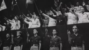 Foto en blanc i negre del jurament de la Secció femenina de la Falange, a primera fila sostenen banderes, a segona fila a un rang més elevat fan la salutació feixista