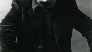 Foto en blanc i negre. Es un retrat de l escriptor Manuel Vázquez Montalbán  assegut en una cadira vestit amb americana i les mans damunt les cames
