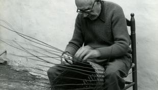 Foto en blanc i negre. Es veu un artesà assegut fabricant amb les seves mans un cistell