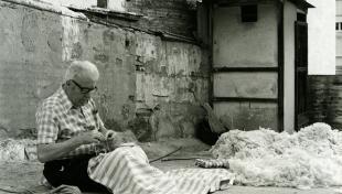 Foto en blanc i negre. Es veu un artesà assegut cosint un matalàs de llana en un terrat