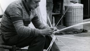 Foto en blanc i negre. Es veu un artesà palmer assegut en el seu taller fent un palmó amb les seves mans