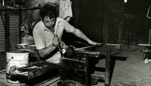 Foto en blanc i negre. Es veu un artesà vidrier assegut en el seu taller bufant vidre per fer una ampolla