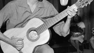 Foto en blanc i negre d'una actuació de Joan Manuel Serrat molt jove amb guitarra i micròfon