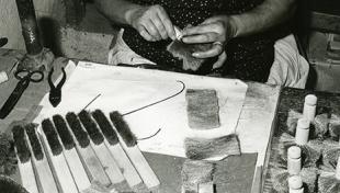 Foto en blanc i negre. Es veu un artesà raspaller assegut fent raspalls