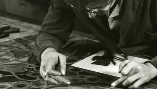 Foto en blanc i negre. Es veu un artesà vitraller assegut posant peces de vidre en un vitrall situat damunt una taula