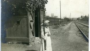 Foto en blanc i negre. Es veu dona que treballa de guardabarreres de tren davant una via