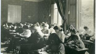 Foto en blanc i negre. Es veu una aula de l'Institut de Cultura per a la Dona amb dones i nenes assegudes davant de pupitres