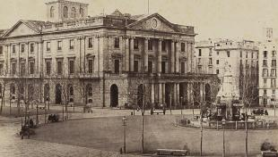 Foto en blanc i negre. Es veu edifici de la Llotja i la plaça Palau a finals de segle dinou