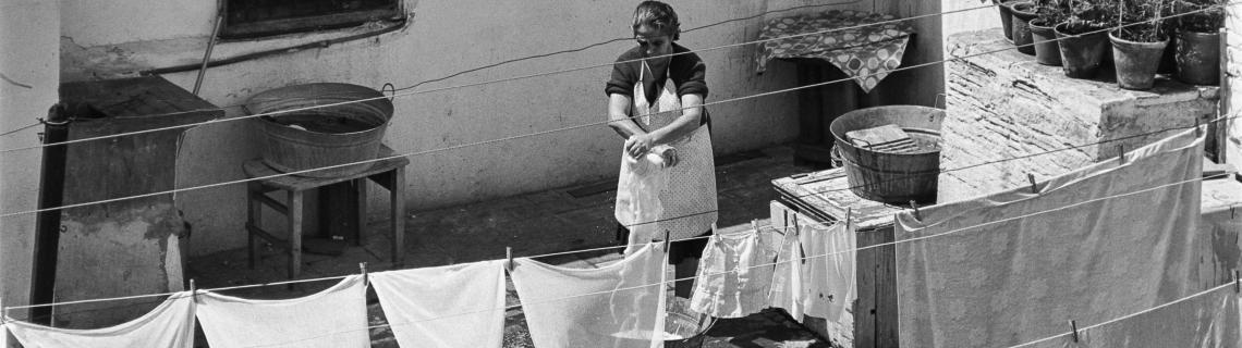 Foto en blanc i negre. Es veu senyora en un terrat estenent llençols i roba blanca
