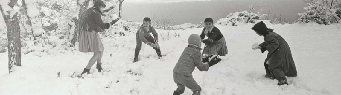 Foto en blanc i negre. Es veu un paisatge nevat amb cinc nens que juguen amb boles de neu