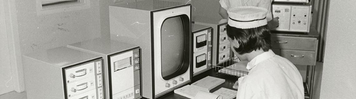 Foto en blanc i negre. Es veu un laboratori de cardiologia amb una infermera asseguda davant pantalles