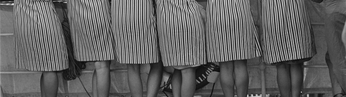 Foto blanc i negre. Es veuen dones d esquena amb bata de ratlles arrenglerades