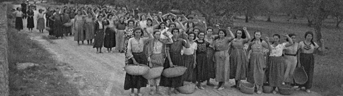 Foto en blanc i negre. Es veu un grup de treballadores del camp aixecant el puny