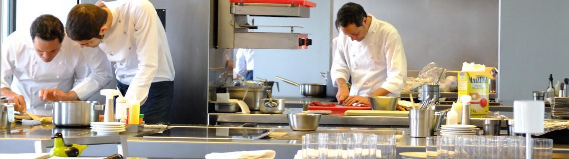 Fotografia color de l'interior de la cuina dels restaurant Dos Cielos on hi ha tres cuiners treballant