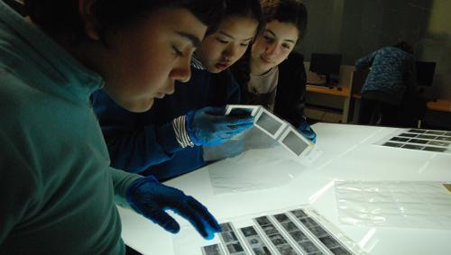 3 alumnes de l'IES Verdaguer mirant negatius de l' Arxiu