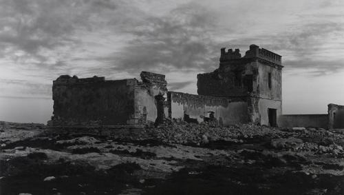Foto en blanc i negre. Es veu un edifici abandonat, en runes, en mig de descampat i envoltat de runes.