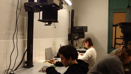 Es veuen 2 joves en el laboratori de fotografia de lArxiu fent un taller