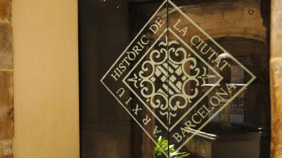 Fotografia de l'escut de l'Arxiu Històric de la Ciutat de Barcelona en la porta d'accés al vestíbul