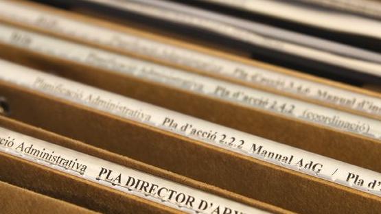 Fotografia on s'observen tot de carpetes penjants col·locades en un calaix obert. Cadascuna de les carpetes està classificada segons la información que conté, com ara el Pla Director d'Arxius o el Manual d'Avaluació